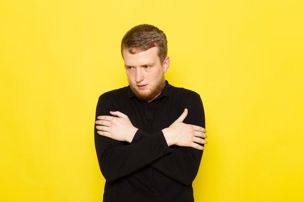 Vista frontal do jovem de camisa preta, posando com expressão trêmula