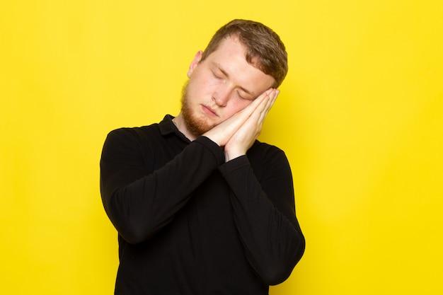 Vista frontal do jovem de camisa preta, posando com gesto a dormir