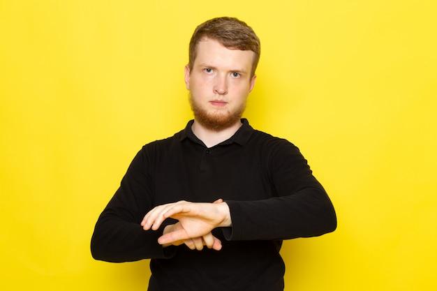 Vista frontal do jovem de camisa preta, posando e apontando para o pulso