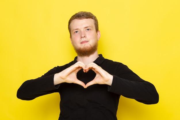 Vista frontal do jovem de camisa preta, posando e mostrando sinal de coração