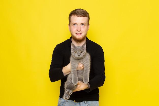 Vista frontal do jovem de camisa preta, segurando o gatinho cinzento bonito com sorriso