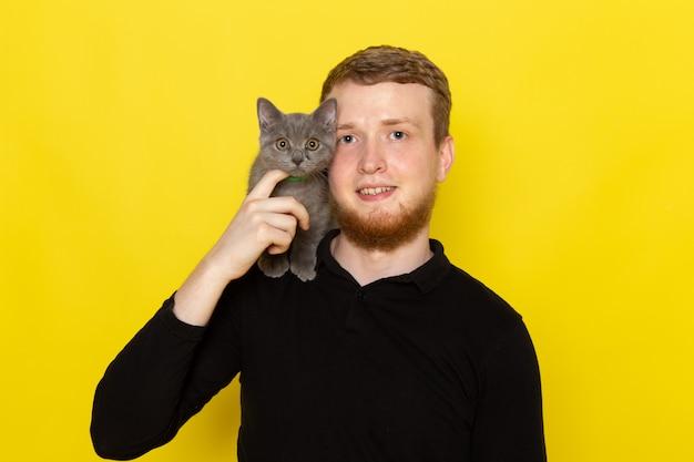 Vista frontal do jovem de camisa preta, segurando o gato cinzento bonito