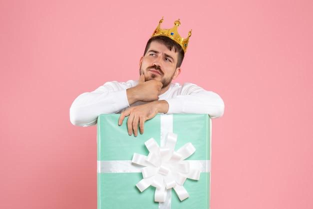 Vista frontal do jovem dentro da caixa de presente com coroa na cabeça pensando na parede rosa