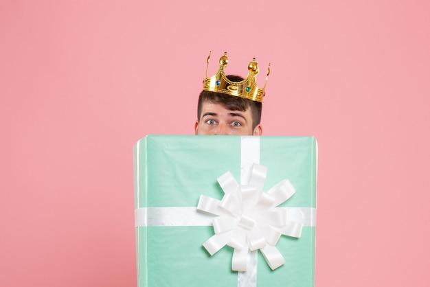 Vista frontal do jovem dentro da caixa de presente com coroa na parede rosa