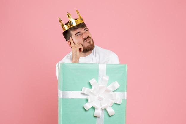 Vista frontal do jovem dentro da caixa de presente com coroa pensando na parede rosa