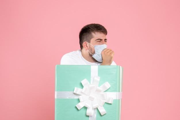 Vista frontal do jovem dentro da caixa de presente com máscara tossindo na parede rosa