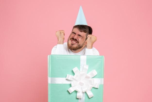 Vista frontal do jovem dentro da caixa de presente na parede rosa