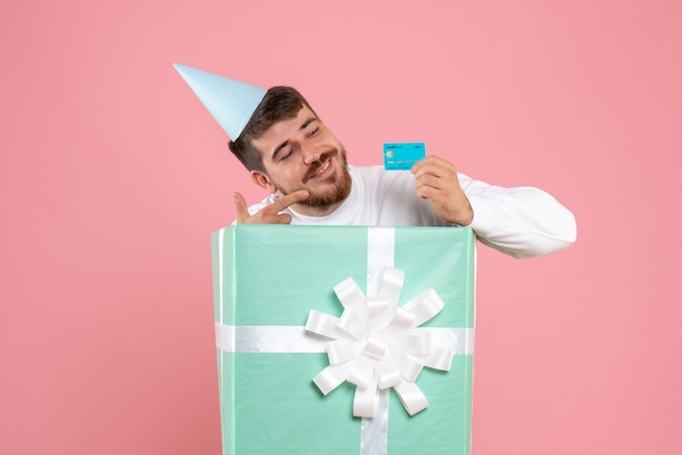 Vista frontal do jovem dentro da caixa de presente segurando o cartão do banco na parede rosa