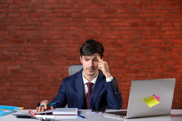 Vista frontal do jovem empresário estressado sentado atrás de seu local de trabalho com o laptop de terno plano de trabalho empreiteiro ocupação construtor trabalho empresarial projeto corporativo