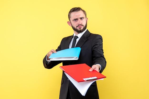 Vista frontal do jovem empresário passando com incerteza a pasta azul e a área de transferência vermelha em amarelo