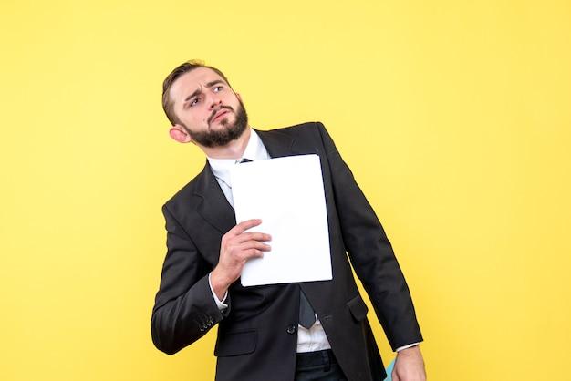 Vista frontal do jovem empresário perplexo, olha de lado e segura o documento em amarelo