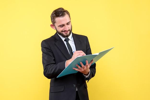 Vista frontal do jovem empresário satisfeito verificando documentos na pasta azul no amarelo