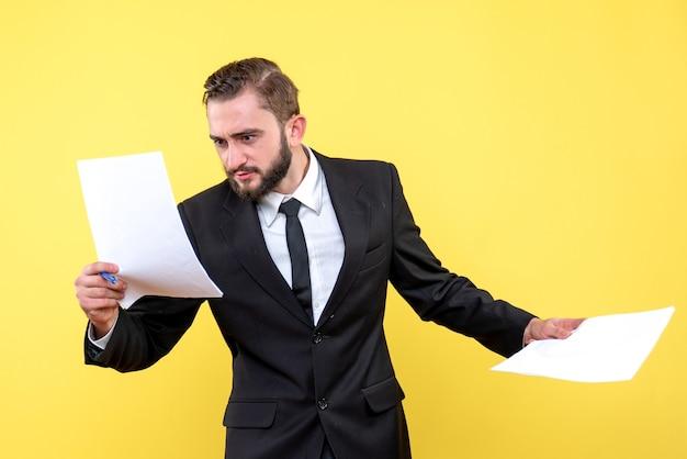 Vista frontal do jovem empresário verificando rapidamente cada documento em amarelo