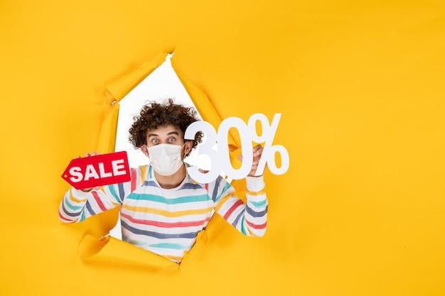 Vista frontal do jovem homem com máscara segurando a cor pandêmica do vírus amarelo, compras vermelho saúde covid foto venda