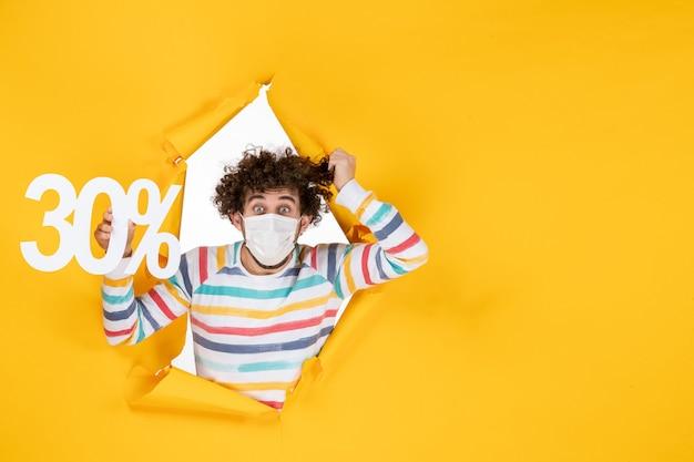 Vista frontal do jovem homem com máscara segurando vírus covidpandêmico de compras de saúde de cor amarela