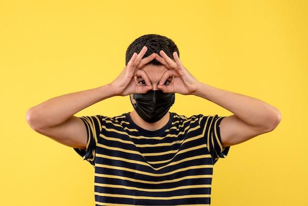 Vista frontal do jovem homem com uma camiseta listrada em preto e branco colocando um sinal de ok na frente de seus olhos sobre fundo amarelo