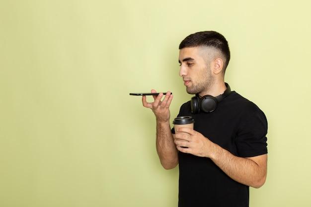 Vista frontal do jovem homem de camiseta preta segurando o telefone e ouvindo música segurando a xícara de café, falando no telefone no verde