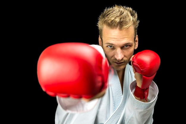 Vista frontal do jovem lutador de boxeador isolado sobre fundo preto.