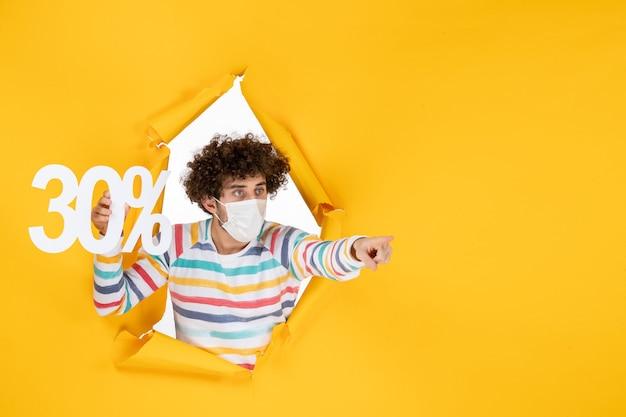 Vista frontal do jovem macho com máscara segurando vírus covid de cor amarela - foto pandêmica