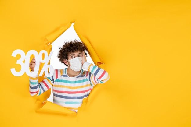 Vista frontal do jovem macho com máscara segurando vírus pandêmico de compras de saúde covid- fotos de cor amarela