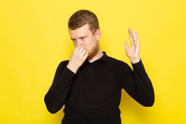 Vista frontal do jovem macho de camisa preta, posando e fechando o nariz devido ao cheiro