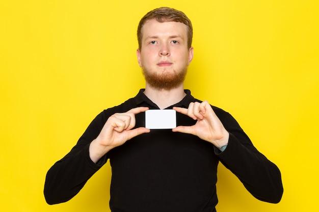 Vista frontal do jovem macho de camisa preta, segurando o cartão branco na superfície amarela