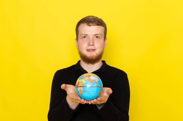 Vista frontal do jovem macho de camisa preta, segurando o pequeno globo com sorriso