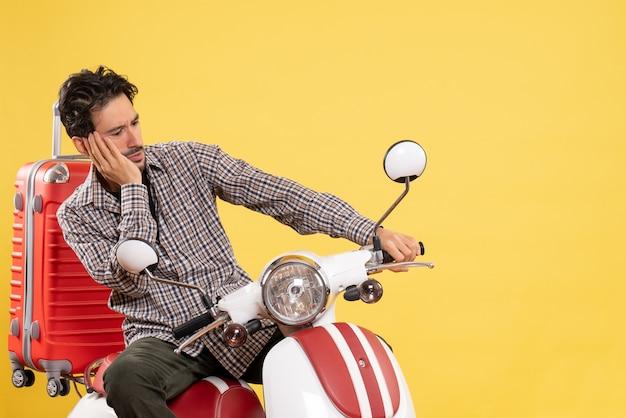 Vista frontal do jovem macho em bicicleta com sua bolsa amarela