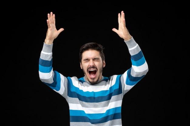 Vista frontal do jovem macho em camisa listrada azul gritando na parede preta