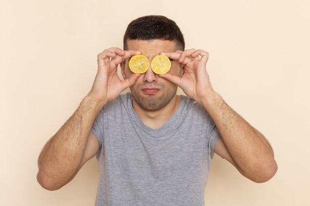 Vista frontal do jovem macho em uma camiseta cinza cobrindo os olhos com rodelas de limão no modelo bege cor de homem