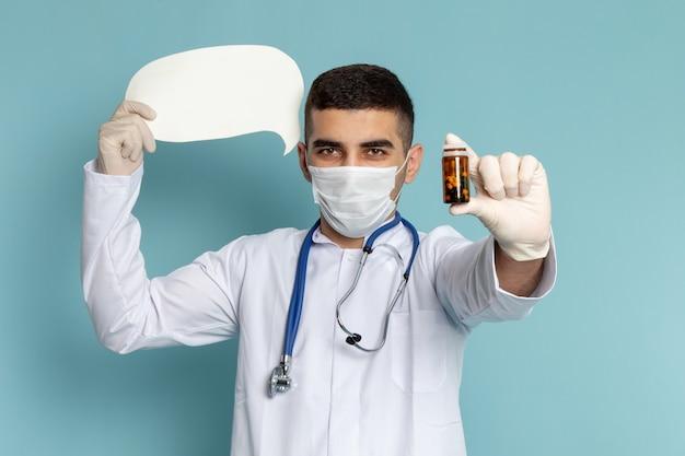 Vista frontal do jovem médico de terno branco com estetoscópio azul segurando comprimidos e placa branca