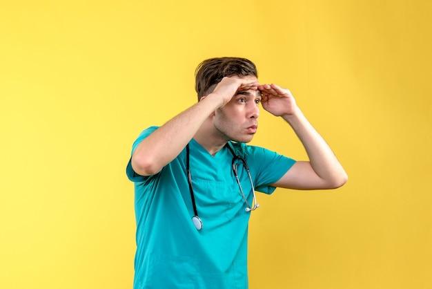 Vista frontal do jovem médico olhando para a distância na parede amarela