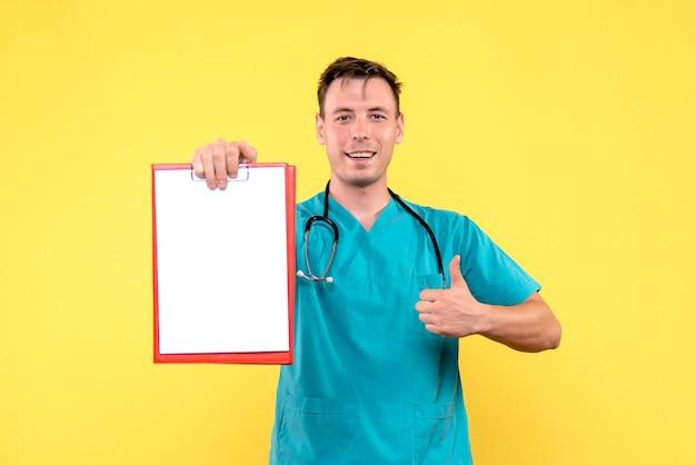 Vista frontal do jovem médico segurando análises na parede amarela