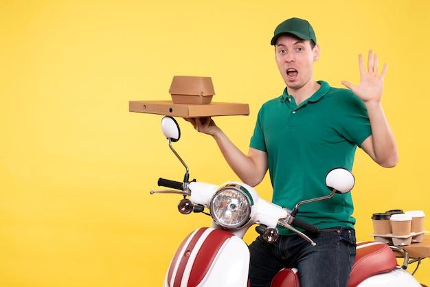 Vista frontal do jovem mensageiro de uniforme segurando pacotes de comida em amarelo