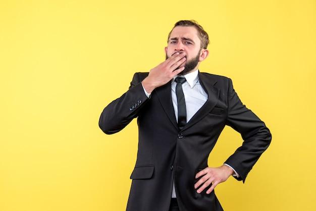 Vista frontal do jovem pensando empresário de mãos dadas na boca amarelo