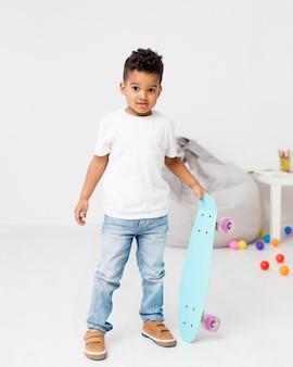 Vista frontal do jovem rapaz com skate