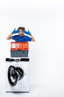 Vista frontal do jovem reparador colocando as mãos na têmpora atrás da máquina de lavar na parede branca