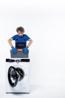 Vista frontal do jovem reparador fechando o saco de ferramentas na máquina de lavar na parede branca