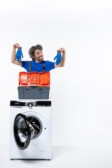 Vista frontal do jovem reparador segurando luvas azuis atrás da máquina de lavar na parede branca