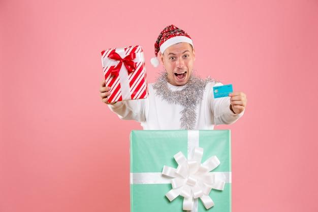 Vista frontal do jovem segurando o presente e o cartão do banco na parede rosa