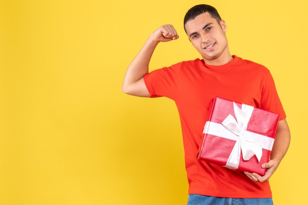 Vista frontal do jovem segurando um presente na parede amarela