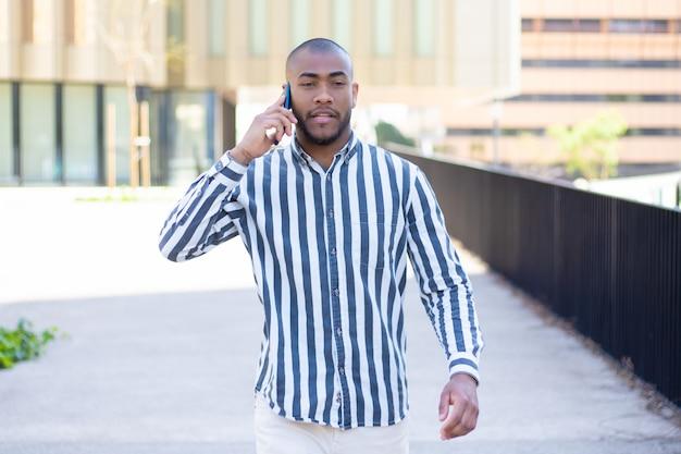 Vista frontal do jovem sério falando no telefone durante passeio