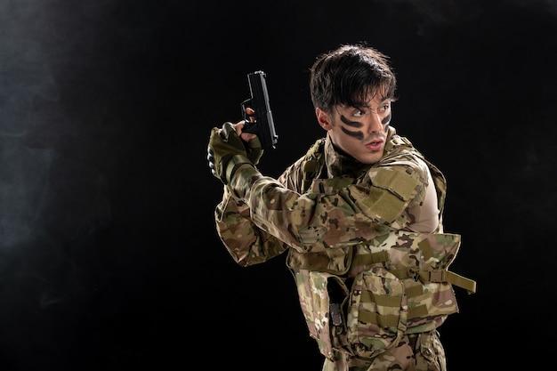 Vista frontal do jovem soldado com arma camuflada na parede preta