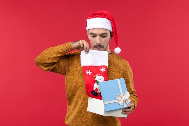 Vista frontal do jovem tirando a meia de natal da caixa na parede vermelha