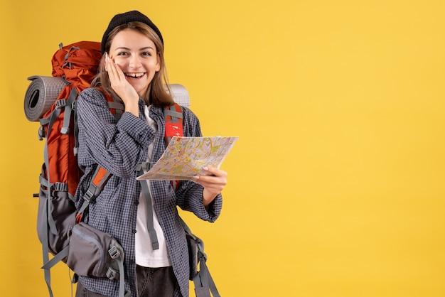 Vista frontal do jovem viajante alegre com a mochila segurando o mapa