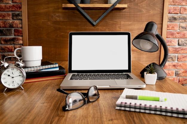 Vista frontal do laptop e da lâmpada na área de trabalho de escritório de madeira