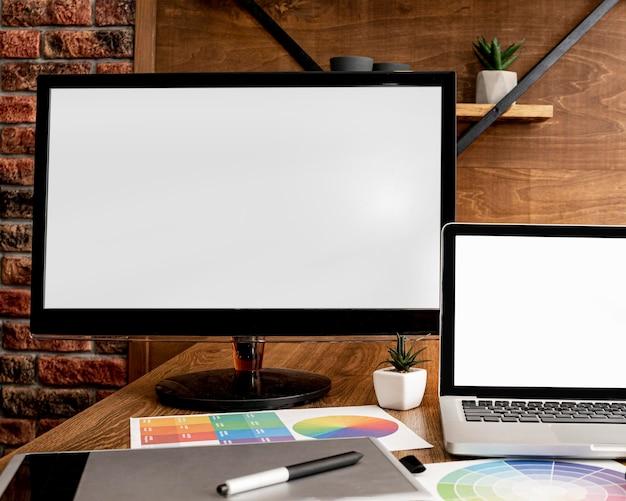 Vista frontal do laptop e do computador na área de trabalho do escritório