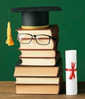 Vista frontal do livro empilhado com boné acadêmico e óculos