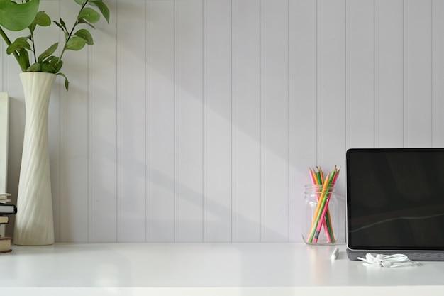 Vista frontal do local de trabalho, copie o tablet de espaço com teclado inteligente na tabela de espaço de trabalho do sotão.
