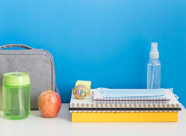 Vista frontal do material escolar com notebook e desinfetante para as mãos
